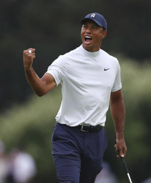 Tiger Woods reacts to his birdie putt on 15 during the second round of the Masters golf tournament Friday