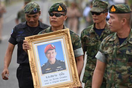 An honour guard hold up a picture of Samarn Kunan, 38, a former member of Thailand's elite navy SEAL unit who died working to save 12 boys and their soccer coach trapped inside a flooded cave, at an airport in Rayong province, Thailand, July 6, 2018. REUTERS/Panumas Sanguanwong