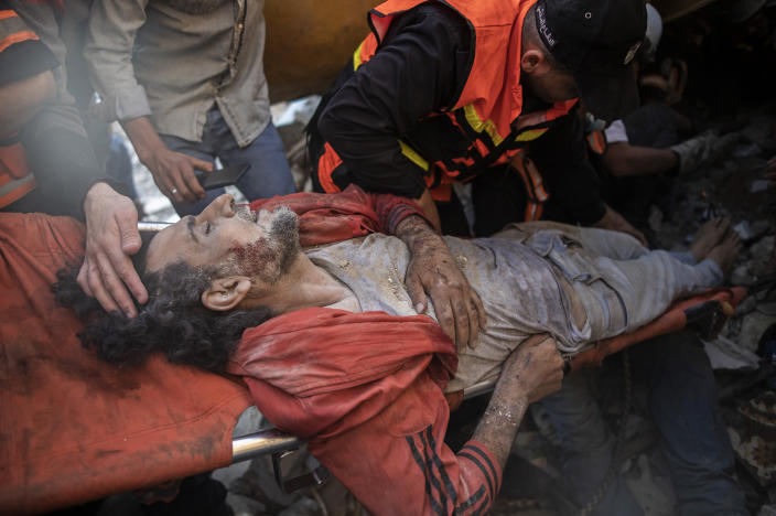 Palestinian rescuers pull a survivor from under the rubble of a destroyed residential building following deadly Israeli airstrikes in Gaza City, Sunday, May 16, 2021. The airstrikes flattened three buildings and killed at least 26 people Sunday, medics said, making it the deadliest single attack since heavy fighting broke out between Israel and the territory's militant Hamas rulers nearly a week ago. (AP Photo/Khalil Hamra)