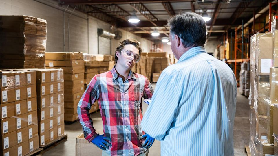 A mature warehouse manager discusses issues with a younger male warehouse worker.
