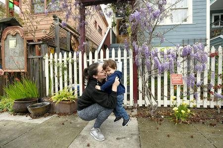 Joy Ashe holds her son Zion Ashe, 1, outside their home in Emeryville, California, United States March 20, 2017. Ashe, who has spoken before the city's planning commission and city council, is concerned about lead and other pollutants from a property renovation across the street from her home. To match Special Report USA-LEAD/CALIFORNIA REUTERS/Noah Berger