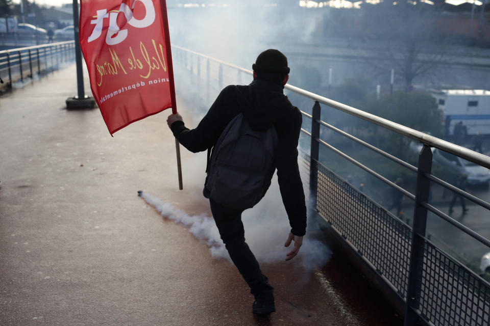 A protestor throws back a teargas canister during a demonstration of unionist and yellow vests, in Creteil, outside Paris, Wednesday, Jan. 9, 2019. About 200 protesters, including unionists and yellow vests, gathered Wednesday in Creteil, a Paris suburb, as Macron was doing a visit in a facility dedicated to handball. Some scuffles broke out with police forces that used tear gas to keep the crowd at a distance from the French leader. (AP Photo/Thibault Camus)
