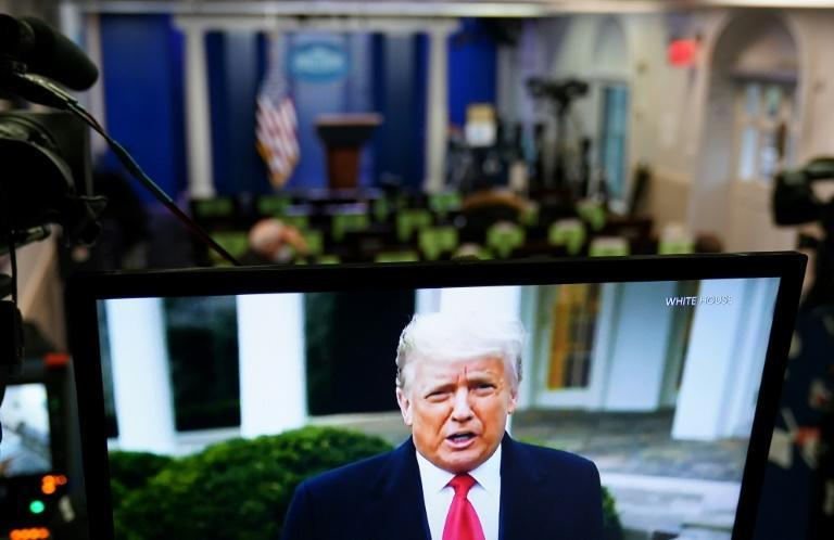 Donald Trump is seen on TV from a video message released on Twitter on January 6 addressing rioters at the US Capitol