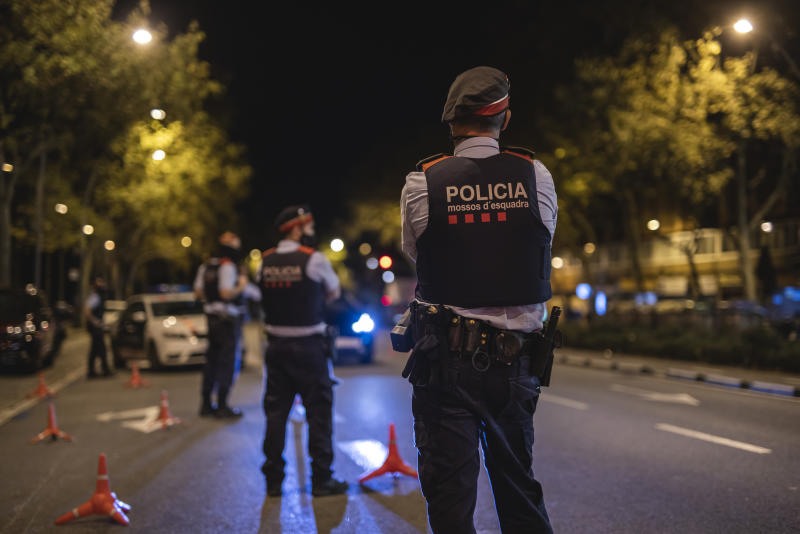 BARCELONA, SPAIN - OCTOBER 25: Police officers stand on patrol on the first night of a countrywide curfew on October 25, 2020 in Barcelona, Spain. Spain has declared a national state of emergency and imposed a night-time curfew from 11pm to 6am in an effort to help control a new spike in coronavirus (COVID-19) infections. (Photo by Xavi Torrent/Getty Images)