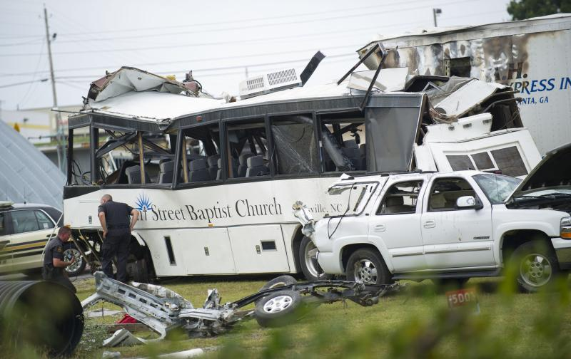 Investigators examine the church bus involved in a fatal Interstate 40 accident Wednesday at a Tennessee Department of Transportation facility in Newport, Tenn., on Thursday, Oct. 2, 2013. Authorities suspect a blown tire caused the bus to cross the median and crash into an SUV and tractor-trailer, killing at least eight people and injuring 14 on Wednesday, Oct. 3, 2013. (AP Photo/Knoxville News Sentinel, Paul Efird)