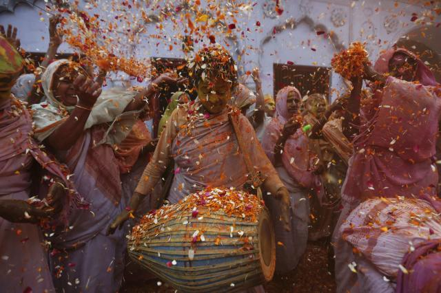 Widows dance as they throw flowers into the air during Holi celebrations organised by non-governmental organisation Sulabh International at a widows' ashram in Vrindavan in the northern Indian state of Uttar Pradesh March 17, 2014. Traditionally in Hindu culture, widows are expected to renounce earthly pleasure so they do not celebrate Holi. But women at the shelter for widows, who have been abandoned by their families, celebrated the festival by throwing flowers and coloured powder. Holi, also known as the Festival of Colours, heralds the beginning of spring and is celebrated all over India. REUTERS/Adnan Abidi (INDIA - Tags: SOCIETY RELIGION TPX IMAGES OF THE DAY)