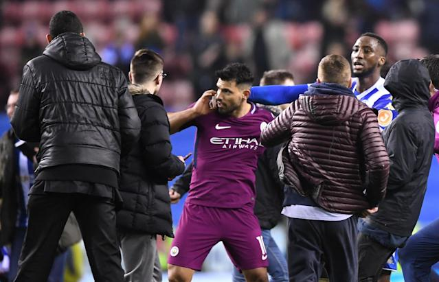 Sergio Aguero is restrained by a Wigan player and a Manchester City staffer during a brief altercation with a Wigan fan. (Getty)