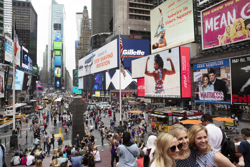 FILE - In this June 20, 2019, file photo, tourists visit Times Square in New York. After three months of a coronavirus crisis followed by protests and unrest, New York City is trying to turn a page when a limited range of industries reopen Monday, June 8, 2020. (AP Photo/Mark Lennihan, File)