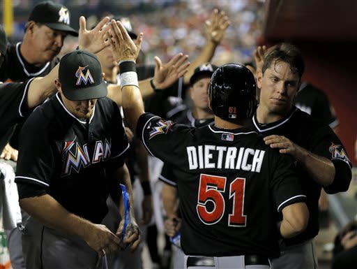 Miami Marlins' Derek Dietrich (51) is greeted in the dugout after scoring on a hit by teammate Adeiny Hechavarria during the fourth inning of a baseball game against the Arizona Diamondbacks, Tuesday, June 18, 2013, in Phoenix. (AP Photo/Matt York)
