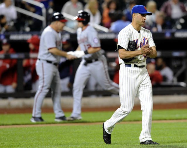 New York Mets pitcher Carlos Torres, right, rubs up a new ball as Washington Nationals' Tyler Moore celebrates with third base coach Trent Jewett, left, as Moore rounds the bases with a home run during the fourth inning of a baseball game, Monday, Sept. 9, 2013, in New York. (AP Photo/Bill Kostroun)