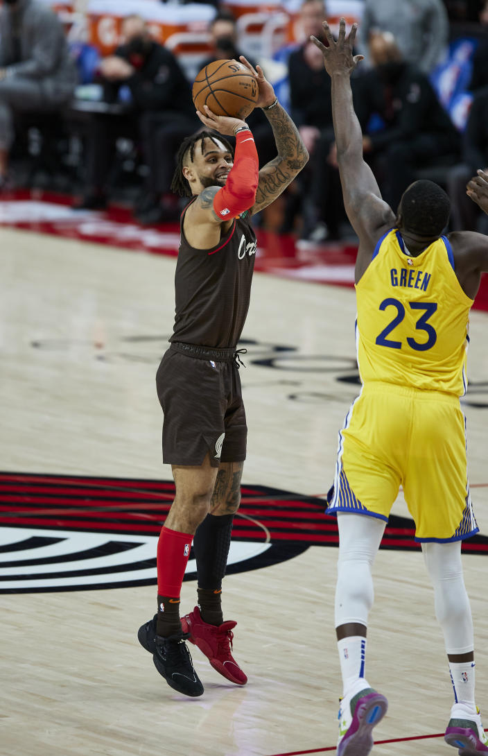 Portland Trail Blazers guard Gary Trent Jr., left, shoots a 3-point basket over Golden State Warriors forward Draymond Green during the second half of an NBA basketball game in Portland, Ore., Wednesday, March 3, 2021. (AP Photo/Craig Mitchelldyer)