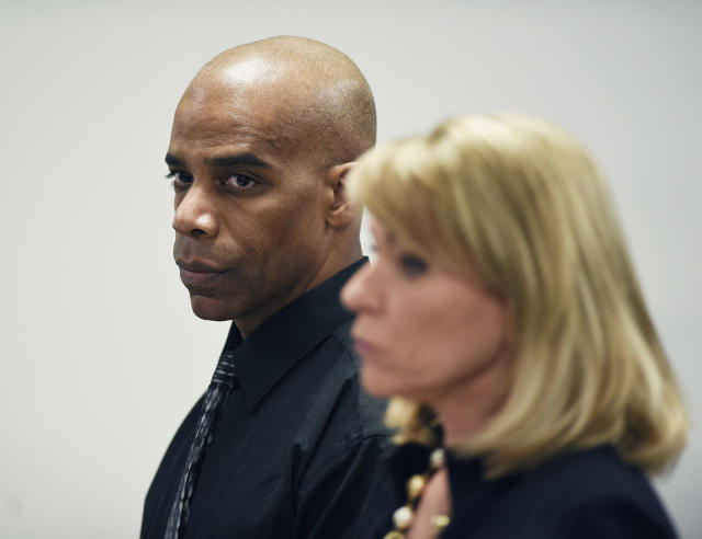 Detroit Police Cpl. Dewayne Jones stands with his attorney Pamella Szydlak as they listen to Judge Cylenthia LaToye Miller during his hearing Tuesday, Jan. 15, 2019 in Detroit. Charges of beating a homeless woman at Detroit Receiving Hospital after she allegedly bit him were dismissed. The judge has dismissed a felony charge against Jones in the beating of a naked, combative woman who prosecutors say was having a mental breakdown inside an emergency room triage unit. He still faces a misdemeanor assault and battery charge. (Clarence Tabb Jr./Detroit News via AP)
