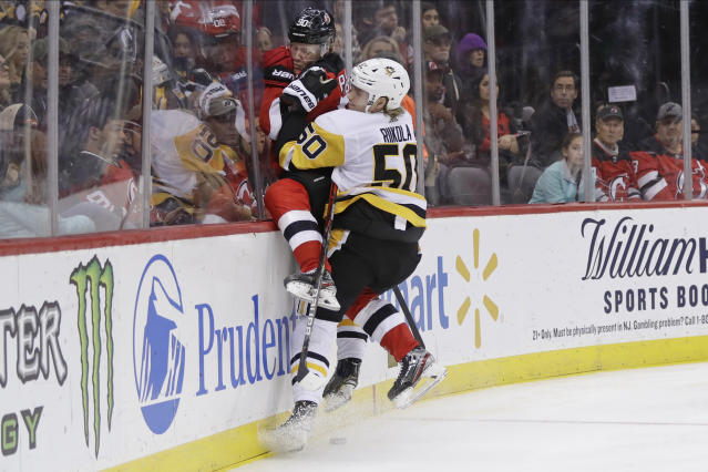 Pittsburgh Penguins' Juuso Riikola (50) checks New Jersey Devils' Jesper Boqvist (90) during the second period of an NHL hockey game Friday, Nov. 15, 2019, in Newark, N.J. (AP Photo/Frank Franklin II)