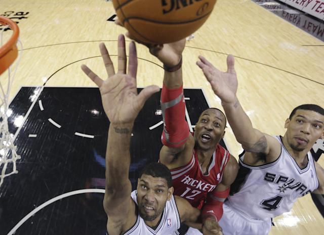 Houston Rockets' Dwight Howard, center, shoots over San Antonio Spurs' Tim Duncan. left, and Danny Green (4) during the first half of a preseason NBA basketball game, Thursday, Oct. 24, 2013, in San Antonio. (AP Photo/Eric Gay)