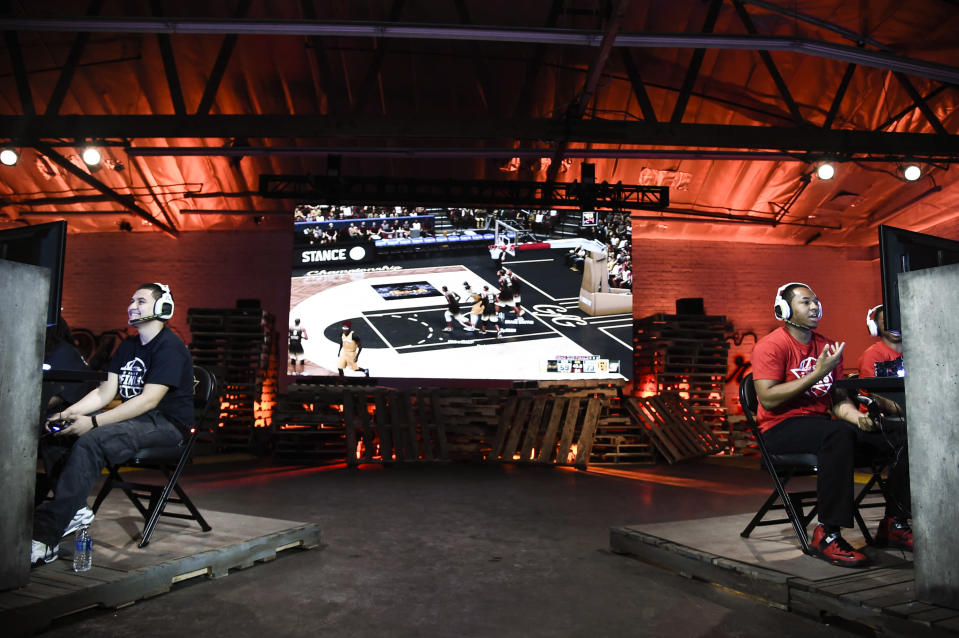 """Team GFG (right) and Team Drewkerbockers (left) compete at the """"NBA 2K16"""" Road to the Finals championship event on June 1, 2016, in Los Angeles. Two teams of gamers went head-to-head for a shot at $250,000 and a trip to the 2015-2016 NBA Finals. (Dan Steinberg/Invision for NBA 2K/AP)"""