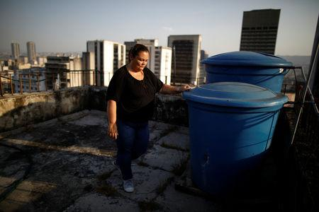Yudith Contreras, a 49-year-old lawyer, who lives on the 9th floor, stands next to her water tanks on the roof her apartment block in downtown Caracas, Venezuela, March 18, 2019. REUTERS/Carlos Garcia Rawlins