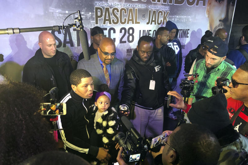 Boxer Gervonta Davis sits with his daughter as he speaks with the media at boxing news conference, Tuesday, Nov. 26, 2019, in Atlanta. Eager to take his career to a higher level, Davis will move up to fight Cuba's Yuriorkis Gamboa for the WBA's secondary lightweight title.  (AP Photo/Paul Newberry)