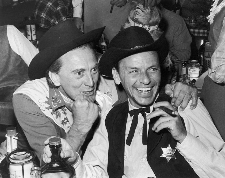 <p>Douglas and Frank Sinatra dressed up in western-themed costumes for a party at the Moulin Rouge in Paris. </p>