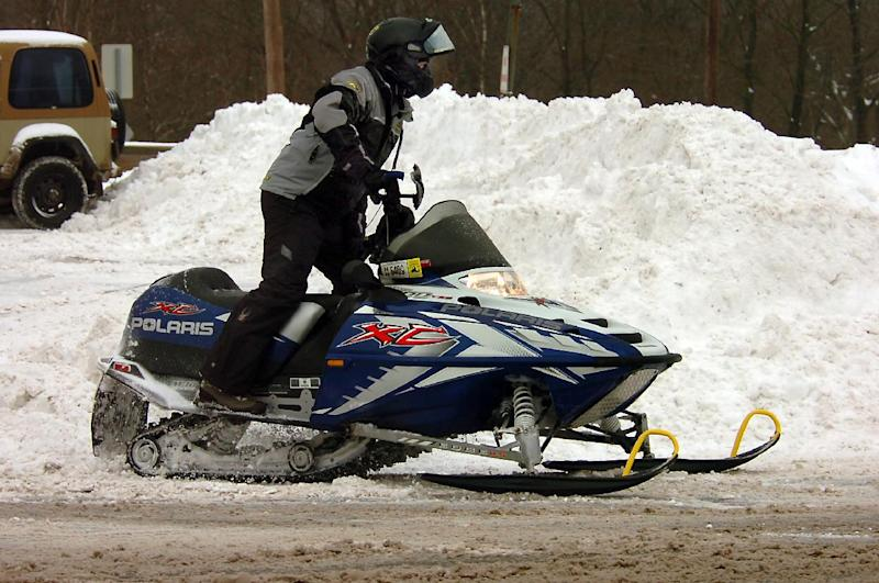 A snowmobiler heads for a trail after getting fuel at a gas station on Main Street in Forest City, Pa., on Wednesday, Feb. 5, 2014, after a winter snow storm. (AP Photo/The Scranton Times-Tribune, Butch Comegys) WILKES BARRE TIMES-LEADER OUT; MANDATORY CREDIT.