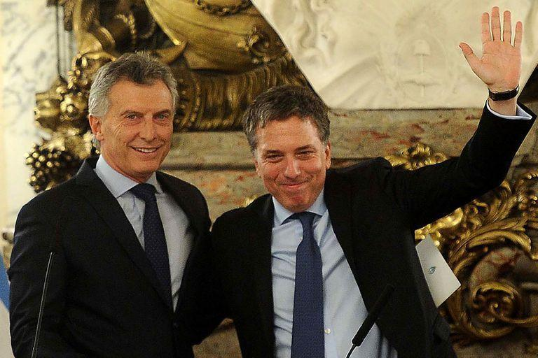 (FILES) In this file photo taken in Buenos on January 10, 2017 Argentine President Mauricio Macri (L) poses with his new Finance Minister Nicolas Dujovne after swearing him in. - Argentine Economy Minister Nicolas Dujovne resigned from his position on August 17, 2019 and will be replaced by Hernan Lacunza, according to Argentinian media reports. (Photo by Florencia DOWNES / TELAM / AFP) / RESTRICTED TO EDITORIAL USE - MANDATORY CREDIT AFP PHOTO /  TELAM-Florencia DOWNES - NO MARKETING - NO ADVERTISING CAMPAIGNS - DISTRIBUTED AS A SERVICE TO CLIENTS