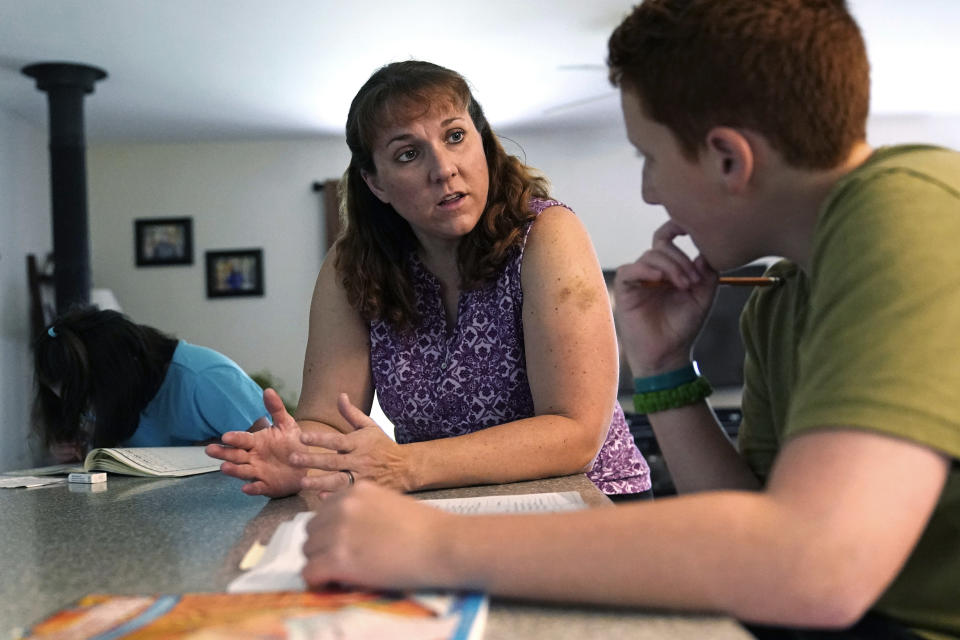 Jennifer Osgood, center, teaches her son, Noah, 12, while reviewing school work at their home in Fairfax, Vt., on Tuesday, July 20, 2021. The U.S. Census Bureau reported in March that the rate of households homeschooling their children rose to 11% by September 2020, more than doubling from 5.4% just six months earlier. (AP Photo/Charles Krupa)