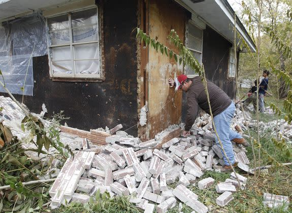 An Oklahoma man cleans up the bricks that fell from three sides of his in-laws home in Sparks, Nov. 6, 2011, after two earthquakes hit the area in less than 24 hours.