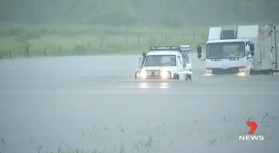 Cars pictured driving through floodwaters in North Queensland.