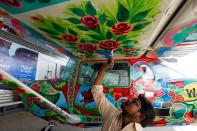Man paints Pakistani truck art on a two-seater Cessna aircraft at Jinnah International Airport in Karachi