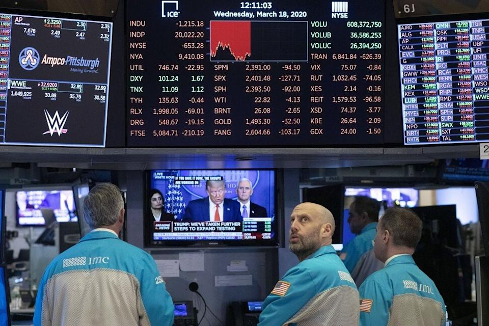 Traders at the New York Stock Exchange watch President Donald Trump's televised White House news conference on March 18, 2020. Photo: AP