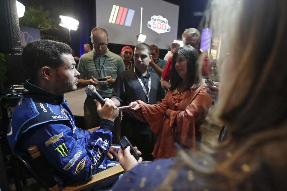 Kyle Larson, left, answers questions from reporters during NASCAR Daytona 500 auto racing media day at Daytona International Speedway, Wednesday, Feb. 12, 2020, in Daytona Beach, Fla. (AP Photo/John Raoux)
