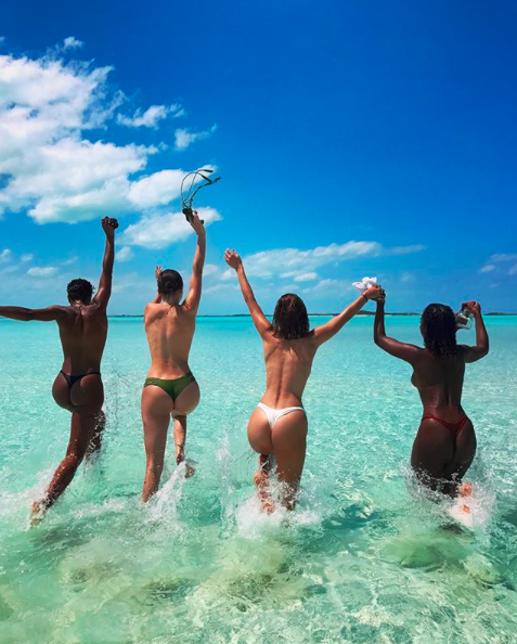 <p>Bella Hadid has posted a throwback snap of herself, Kendall Jenner and other models going topless and wearing G-string bikini bottoms while jumping into the ocean at a tropical location.</p>