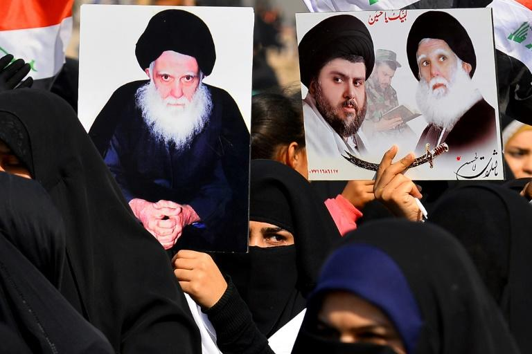 Women in Iraq's central city of Kufa hold up posters showing Moqtada Sadr (centre) and his father Ayatollah Mohammed Sadeq al-Sadr, killed under Saddam Hussein's regime in 1999