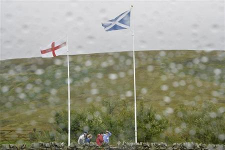 Scottish and English flags flutter in the wind and rain at the border between England and Scotland at Carter Bar
