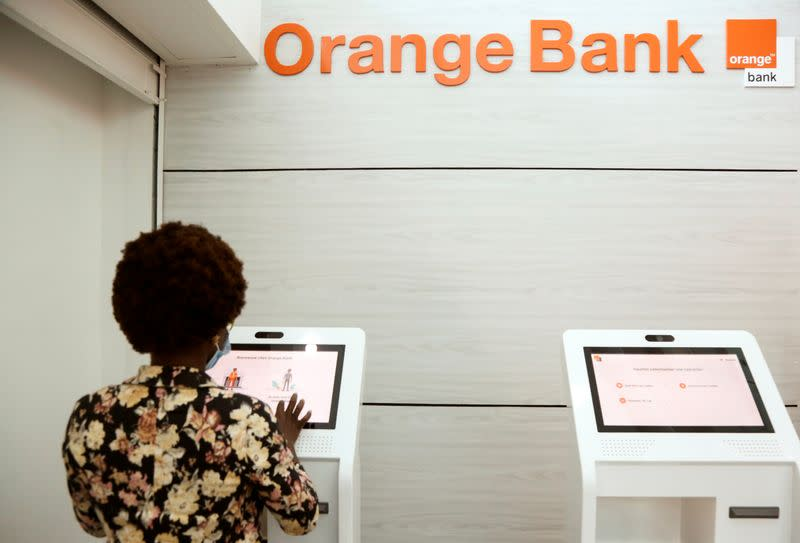 A woman performs a financial transaction at a bank of the French mobile operator Orange in Abidjan, Ivory Coast