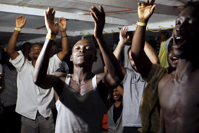 Migrants onboard the Open Arms vessel celebrate the news of an Italian prosecutor who has ordered that the migrants be disembarked on the island of Lampedusa, southern Italy, Tuesday, Aug. 20, 2019. At least 15 more migrants jumped into the sea Tuesday from the Open Arms rescue ship in desperate bids to reach the shores of Italy after 19 days of being on the boat in deteriorating conditions as Italy refuses to open its ports. (AP Photo/Francisco Gentico)