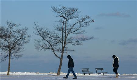 Residents brave the cold as they walk along the shores of Lake Michigan as another round of arctic air blasts the midwest keeping the wind chill in the negative numbers Milwaukee Wisconsin