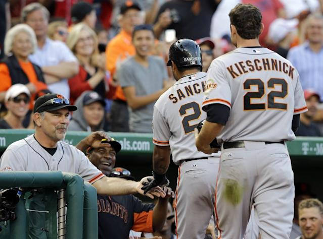 San Francisco Giants manager Bruce Bochy, left, celebrates with Hector Sanchez (29) after Sanchez's three-run homer during the ninth inning of a baseball game against the Washington Nationals at Nationals Park on Thursday, Aug. 15, 2013, in Washington. The Giants won 4-3. (AP Photo/Alex Brandon)