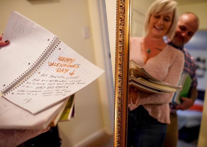 Susan Fenske sifts through notebooks she and her husband, Bret, filled with love notes at their apartment in Clarksville, Tenn., on Feb. 4.