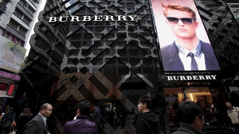 People walking outside a Burberry store in the Tsim Sha Tsui shopping district of Hong Kong