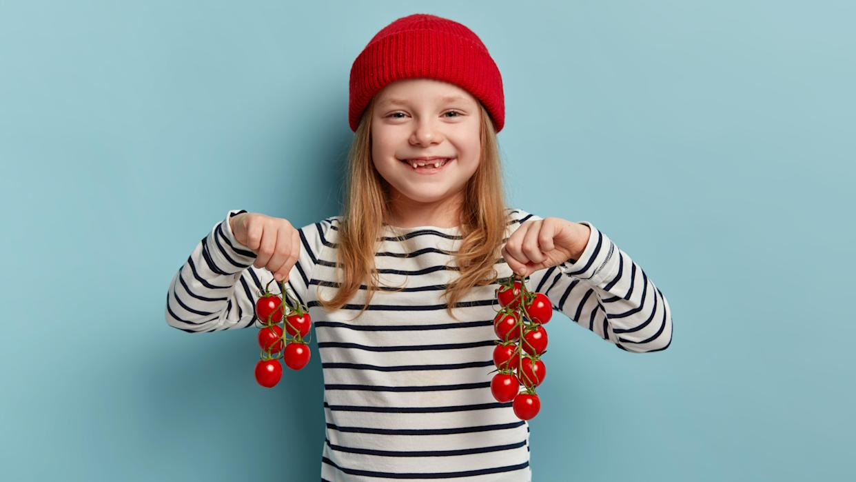 Harvesting vegetables concept. Adorable small child in red hat and striped sweater, carries red cherry tomatoes, likes working in garden, eats fresh healthy domestic products, stands indoor.