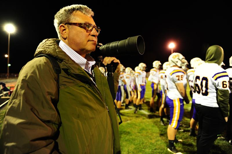 "In this photo taken Friday, Oct. 18, 2013, self-employed photographer Michael Weaver works the sidelines of a high school football game in Jerseyville, Ill. It took him about a week and a half, but Weaver kept going back to the healthcare.gov website until he opened an account and applied for a tax credit that will reduce his health care premiums. ""We need to stop the arguing and move forward to make it work,"" he says. In his mid-50s, with high blood pressure, high cholesterol, but otherwise good health, Weaver said those conditions made it hard for him to get coverage previously. (AP Photo/Michael Thomas)"