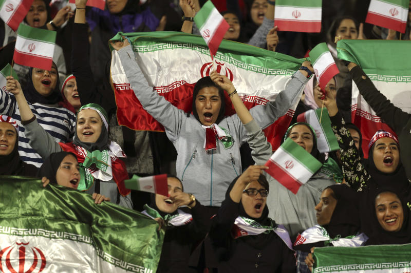 "FILE - In this Oct. 16, 2018 file photo, Iranian women cheer as they wave their country's flag after authorities in a rare move allowed a select group of women into Azadi stadium to watch a friendly soccer match between Iran and Bolivia, in Tehran, Iran. Sahar Khodayari, an Iranian female soccer fan died after setting herself on fire outside a court after learning she may have to serve a six-month sentence for trying to enter a soccer stadium where women are banned, a semi-official news agency reported Tuesday, Sept. 10, 2019. The 30-year-old was known as the ""Blue Girl"" on social media for the colors of her favorite Iranian soccer team, Esteghlal. (AP Photo/Vahid Salemi, File)"