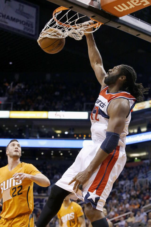 Washington Wizards' Nene, right, of Brazil, dunks as Phoenix Suns' Miles Plumlee (22) looks on during the first half of an NBA basketball game, Friday, Jan. 24, 2014, in Phoenix. (AP Photo/Ross D. Franklin)