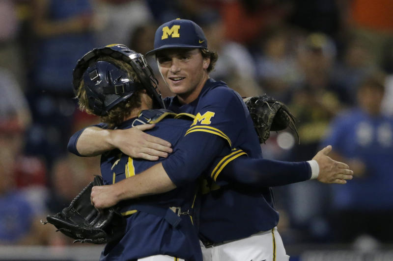 Michigan pitcher Tommy Henry, right, is hugged by catcher Joe Donovan after pitching a complete game against Florida State in an NCAA College World Series baseball game in Omaha, Neb., Monday, June 17, 2019. (AP Photo/Nati Harnik)