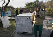 Pakistani wildlife workers and experts from the international animal welfare organization Four Paws, gather next to a crate to be used for transporting a sick brown bear, at the Marghazar Zoo, in Islamabad, Pakistan, Wednesday, Dec. 16, 2020. A pair of sick and badly neglected dancing Himalayan brown bears will leave Islamabad's notorious zoo Wednesday for a sanctuary in Jordan, closing down a zoo that once housed 960 animals. The Marghazar Zoo's horrific conditions gained international notoriety when Kaavan, dubbed the world's loneliest elephant, grabbed headlines and the attention of iconic American entertainer Cher. (AP Photo/Anjum Naveed)