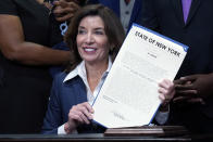 """New York Gov. Kathy Hochul holds the """"Less is More"""" law she signed, during ceremonies in the her office, in New York, Friday, Sept. 17, 2021. New Yorkers will be able to avoid jail time for most nonviolent parole violations under a new law that will take effect in March, and largely eliminates New York's practice of incarcerating people for technical parole violations. (AP Photo/Richard Drew)"""
