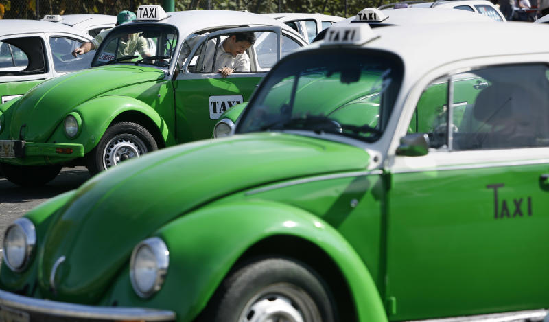 FILE - In this Dec. 28, 2007 file photo, a man steps out of his Volkswagen beetle taxi during an inspection in Mexico City.  Mexico City has announced that the last of the iconic Volkswagen Beetle taxis will be withdrawn from service by the end of 2012. (AP Photo/Gregory Bull, File)