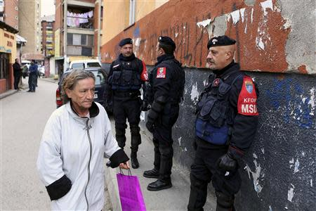 A woman passes by Italian Carabinieri, who are members of the NATO Kosovo Force (KFOR), in the northern part of the ethnically-divided town of Mitrovica November 17, 2013. REUTERS/Bojan Slavkovic