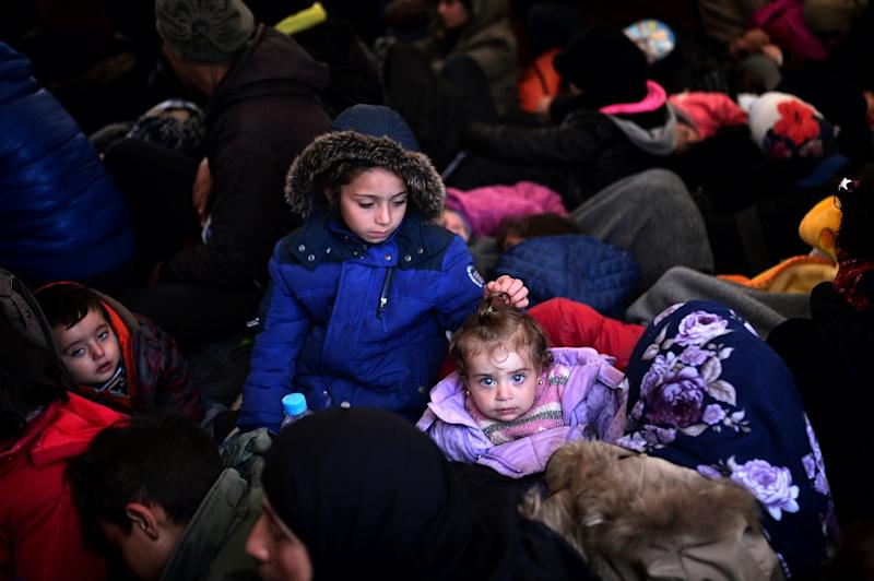 Migrants and refugees sit in an overcrowded tent on March 7, 2016 after waiting overnight at the Greek-Macedonian border (AFP Photo/Louisa Gouliamaki)