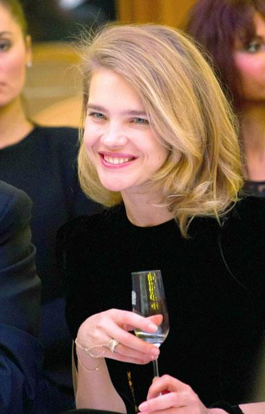 Natalia Vodianova sipped a glass of champagne as she sat stylish on the FROW for the Yanina collection © Rex